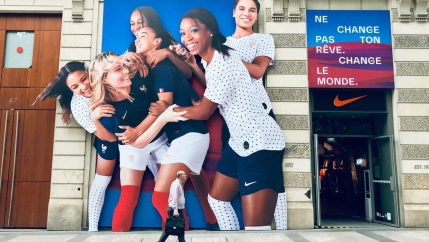 A manis shown with a briefcase walking past a billboard showing members of the French Women's World Cup soccer team hugging.