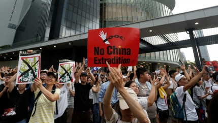 Thousand of people are shown in the streets of Hong Kong with several holding placards.
