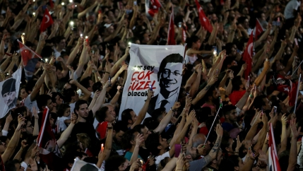 Hundres of people are shown with their hands in the air holding lighters and Turkey flags with a white sign in the middle with a portrait of Ekrem İmamoğlu on it.