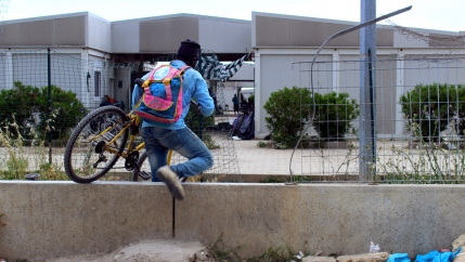Young man crawls through fence with bicycle