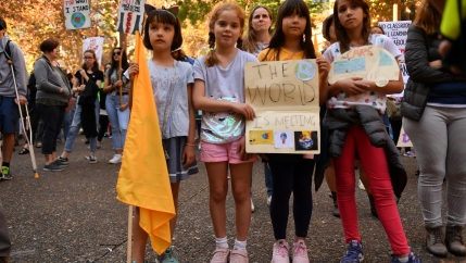Children hold up signs protesting climate change.