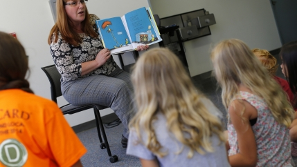 a teacher reads a book to a group of student.