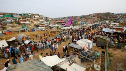 Rohingya refugees stand in a makeshift refugee camp made mostly of tents.