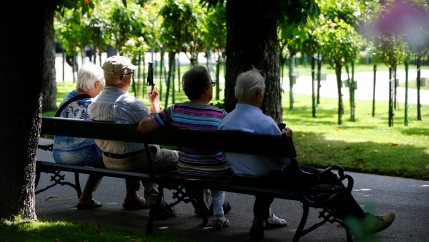 Four elderly people sit on a park bench.