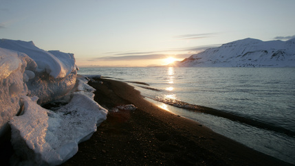 The sun sits above the horizon over melting ice in the arctic by the ocean in the arctic.