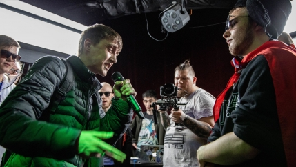 A camera man films two rappers battling.