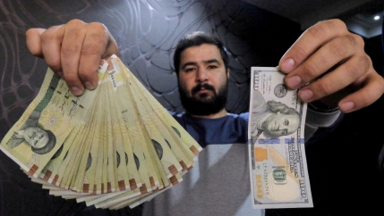 A man holds Iranian and American currency