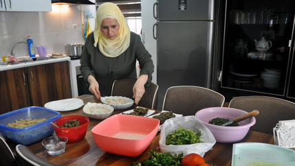 A woman stands over a spread of dishes in the kitchen