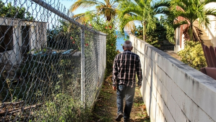 A man is shown walking between two houses with a chain link fence on his left and a manicured stone wall on his right.