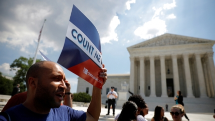 A man stands in front of the US Supreme Court building holding a sign that says
