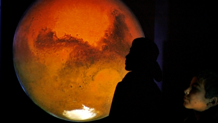 a boy looks at a projection of Mars