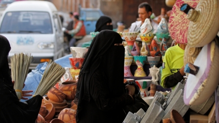 Women in black hijab shop at market in Sanaa, Yemen