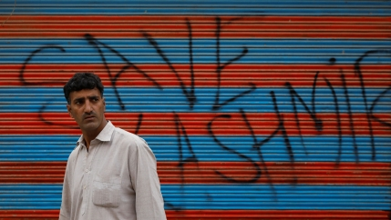 A man walks in front of a wall spray painted with the words