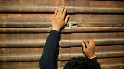 A persons hands hand onto the metal of the border wall