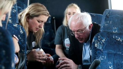 Bernie Sanders sits in a bus next to a woman, a diabetes patient