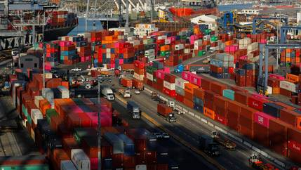 Hundreds of brightly colored shipping containers are stacked around a port