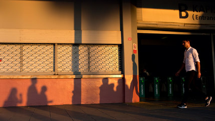 A man is shown walking in front of a metro stop in Istanbul at dusk with the long shadow of several other people on the wall.