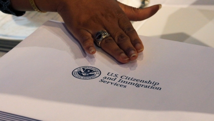 A close up of a hand and a USCIS folder