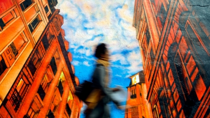 A woman walks by a mural in New York.