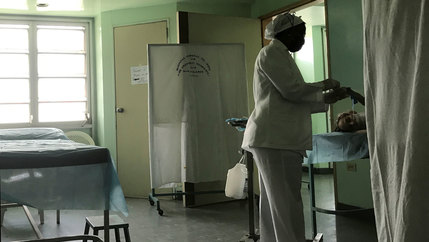 A nurse treats a TB patient on a hospital bed
