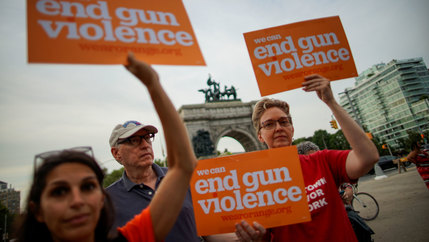 People gather for a vigil to remember victims of the mass shootings at Dayton and El Paso and hold placards that read,