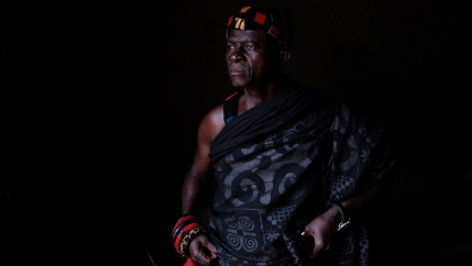 An older man is shown looking off and wearing a traditional wrap along with several bracelets and a watch.