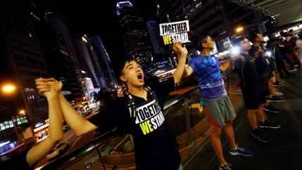 People stand holding hands and signs reading 'together we stand' in front of a nighttime cityscape