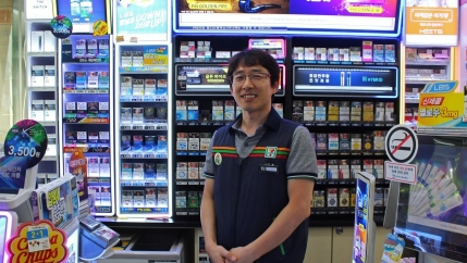Man stands in 7-Eleven in work vest