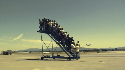 A group of people is seen on a mobile staircase at an airport.