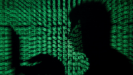 Man holds laptop computer as cyber code is projected on him in an illustration picture.