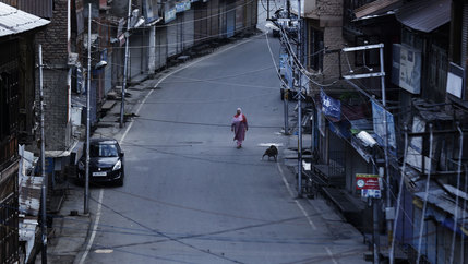 A Kashmiri woman walks on a deserted road in Srinagar.