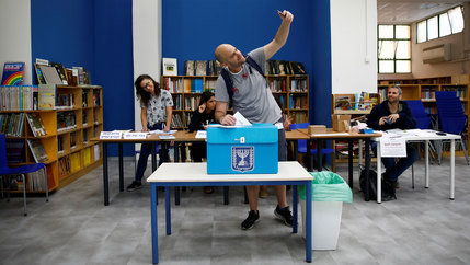 A man holds his cell phone above his head for a selfie with the ballot box