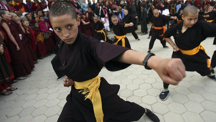 A Buddhist nun with a shaved head takes part in a Kung Fu display