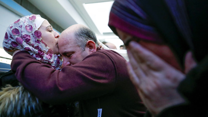Syrian refugees embrace after landing at Chicago's O'Hare airport.