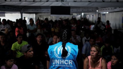 A member of United Nations High Commissioner for Refugees (UNHCR) talks with Venezuelans as they queue in line to receive a vaccine after showing their passports or identity cards at the Pacaraima border control, Roraima state, Brazil, on Aug. 8, 2018.