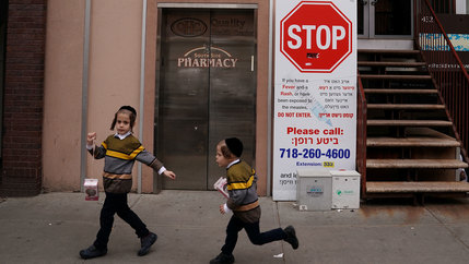 Two children are shown wearing matching stripped sweaters and running past a poster featuring a large stop sign.