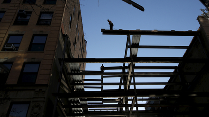 workers install US steel beams against sunlight in construction of building