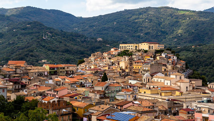 An old Italian town of San Piero Patti is shown from above with the rooftops of homes built into the lush green hillside.