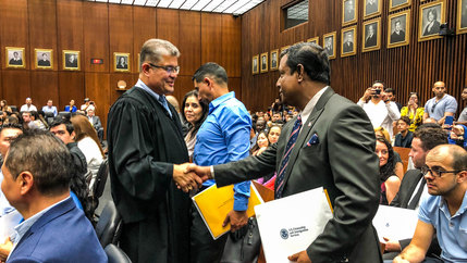 A judge shakes hands with a man at his citizenship ceremony