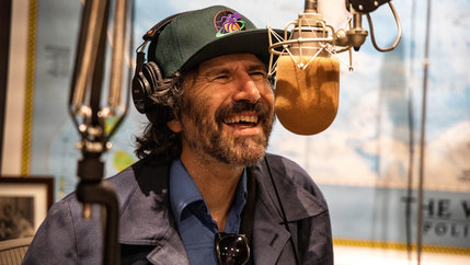 A white man in a hat laughs into a radio mic