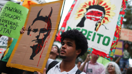 A person holds a placard with a drawing depicting Brazil's President Bolsonaro with horns during a Global Climate Strike rally in Rio de Janeiro