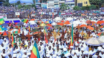 A mass of protesters wearing white and carrying Ethiopian flags gather in the street