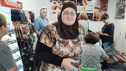 A woman stands with smartphone in a shop with organizers
