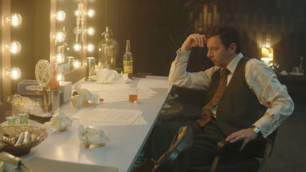 A film still of a man sitting at a dressing room mirror with lights