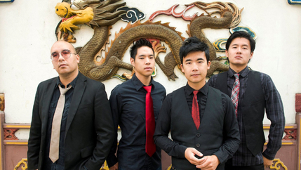 Four young men pose for a photo in front of a wall with the painting of a dragon.