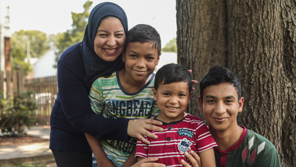 A woman in a hijab smiles and poses with three boys ranging in age