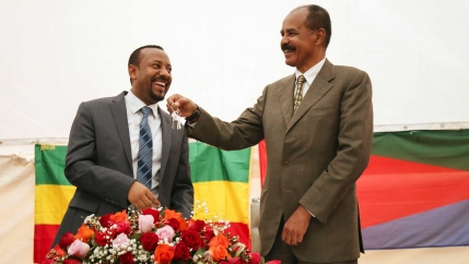 A man smiles as another man dangles keys from his hand. Behind the pair are the flags of Ethiopia and Eritrea.