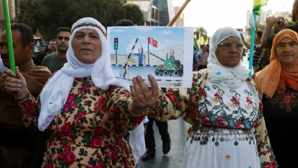 Older women hold a cartoon graphic depicting Donald Trump and a Turkish tank.