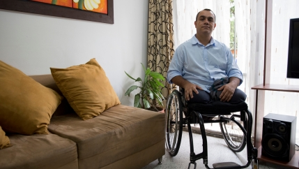 A man with no legs sits in a wheelchair in his living room