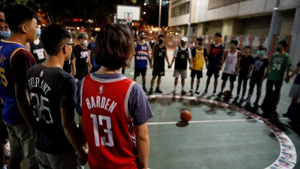 A ring of protesters in basketball uniforms